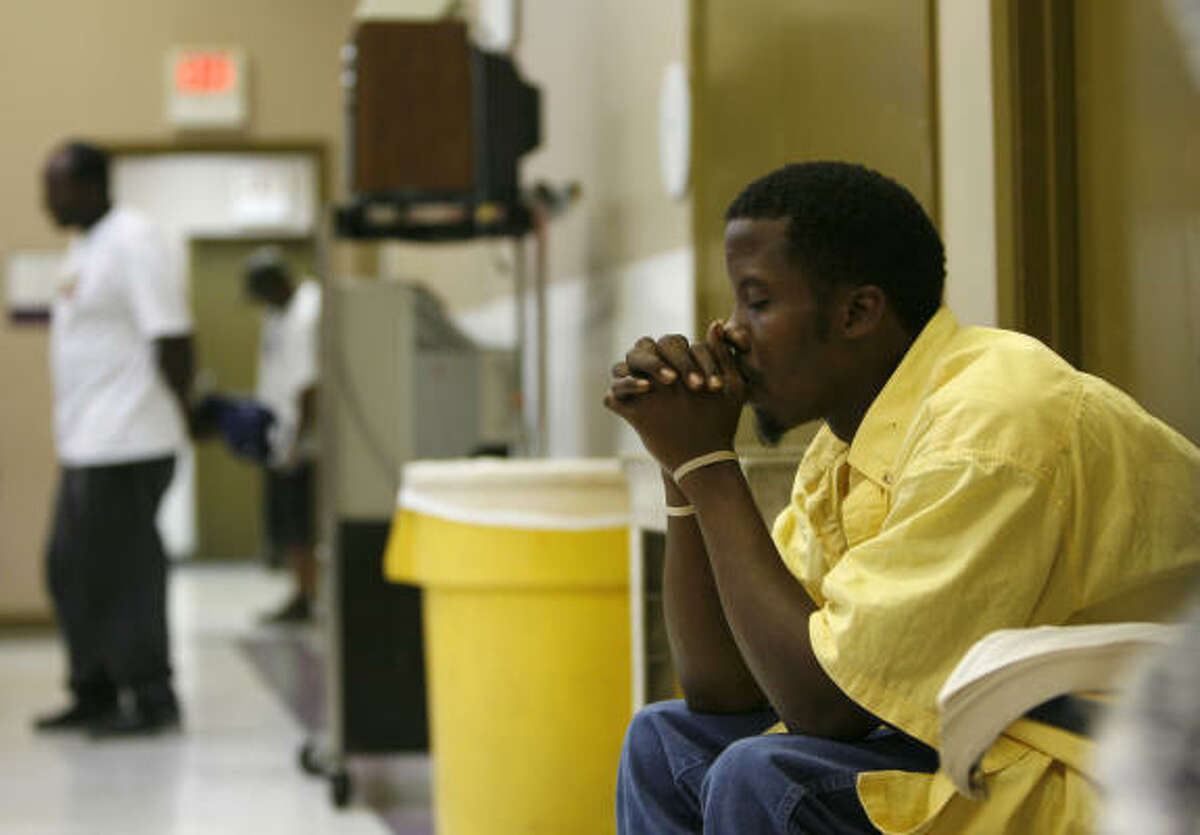 Derrick Proctor, 29, prays before dinner at the Bread of Life's After Dark program. Bread of Life, a nonprofit arm of St. John's Downtown church, became Houston's first homeless program to open through the night for what's called the