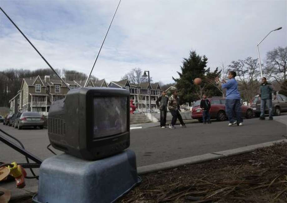 "Children play with a ball near a television set equipped with a traditional ""rabbit ears"" antenna in Seattle this week. U.S. stations were to halt analog signals on Friday. Photo: Ted S. Warren, AP"