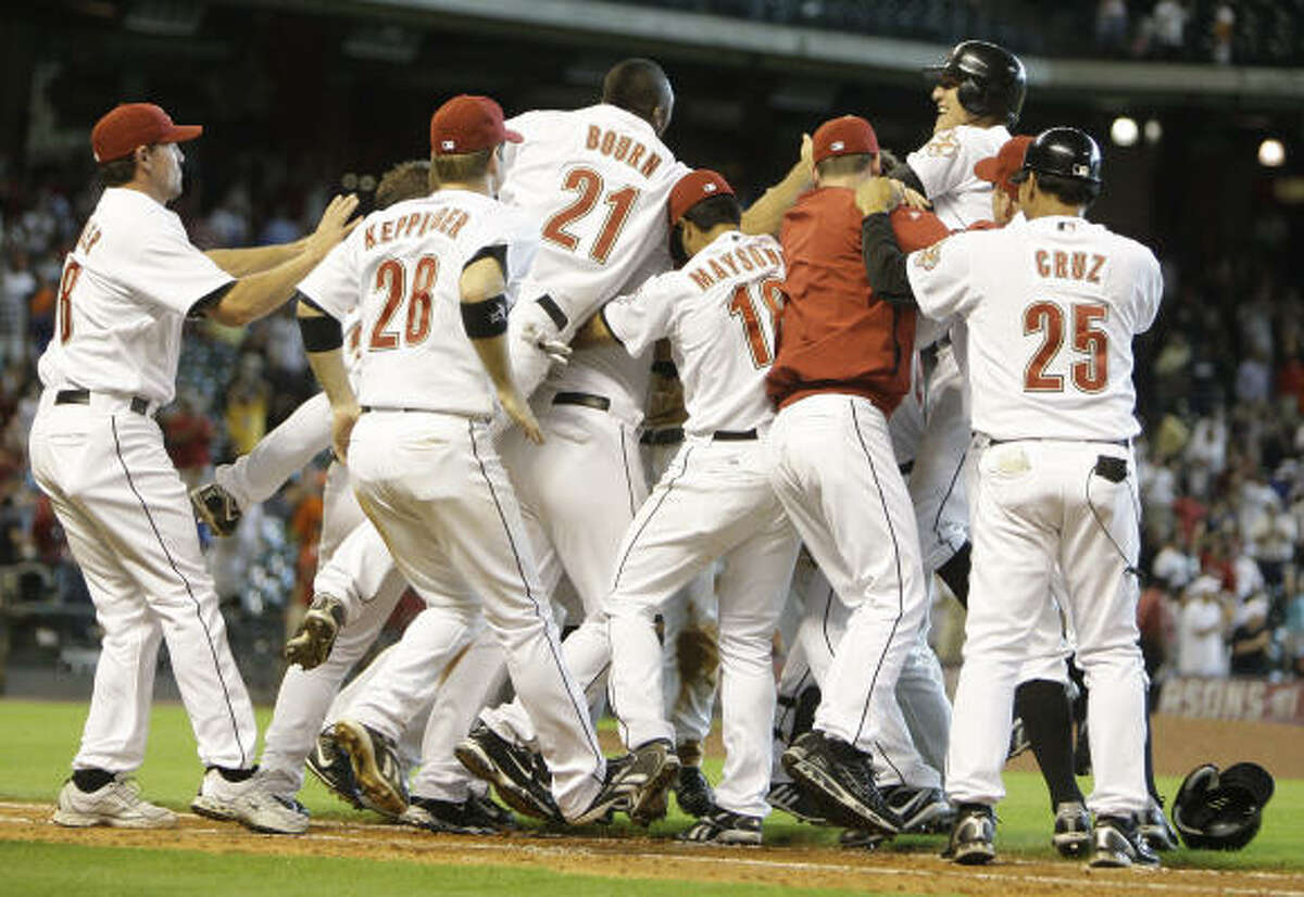 Astros players mob Geoff Blum after his walk-off single to score Hunter Pence beat the Chicago Cubs during the 13th inning.
