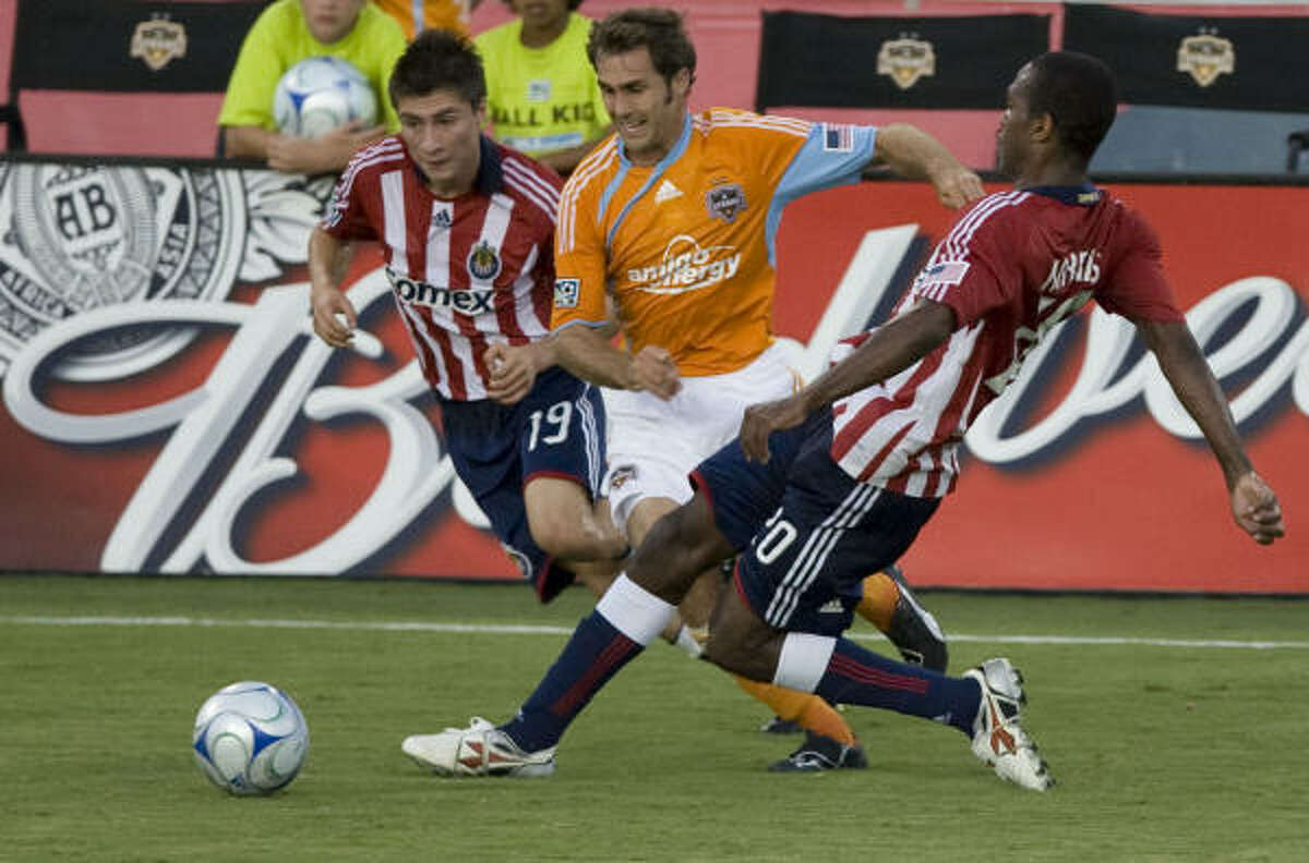 The Houston Dynamo's Brian Mullen, center, and Chivas USA's Jorge Flores, left, and Atiba Harris, right, during the first half.