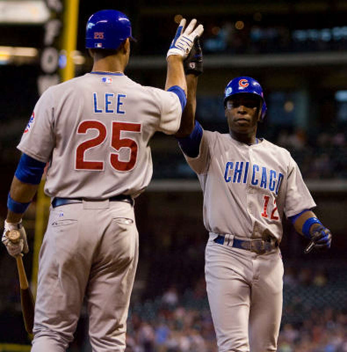 Chicago Cubs first basemen Derrek Lee celebrates a run scored by Cubs outfielder Alfonso Soriano in the first inning.