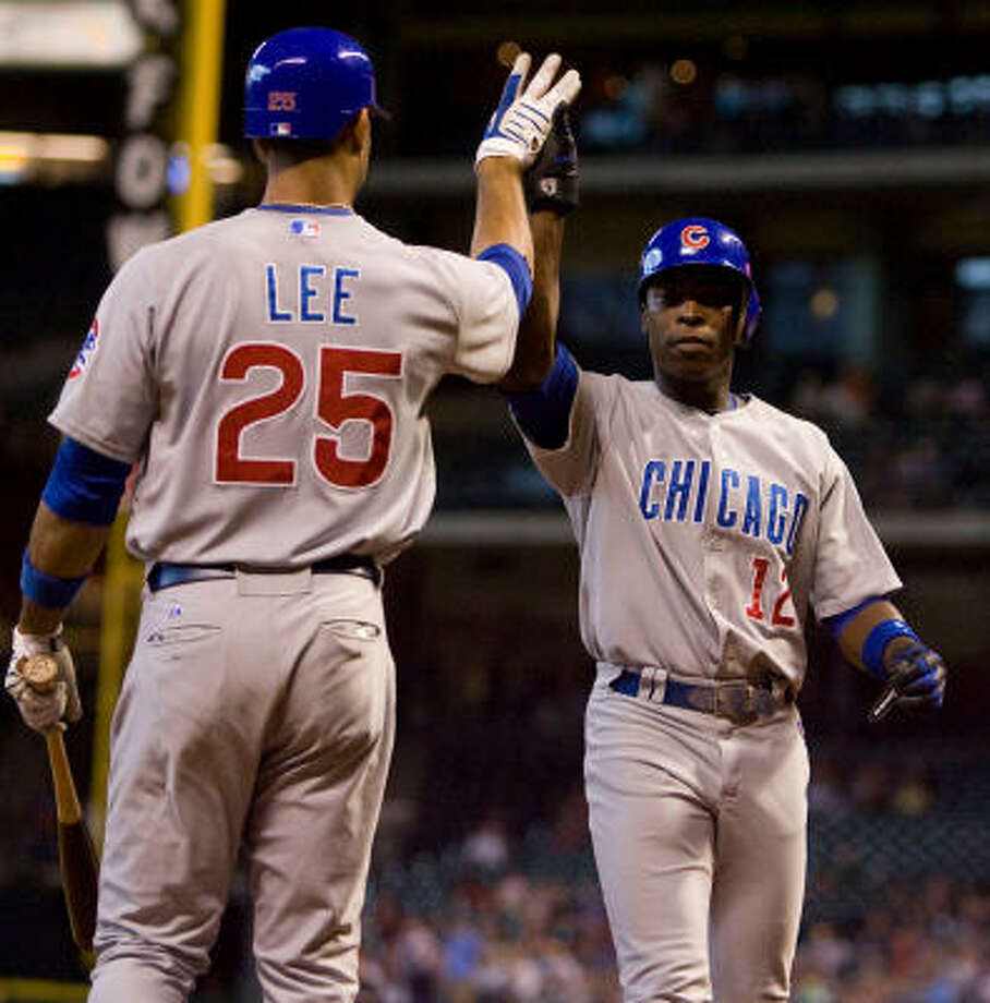 Chicago Cubs first basemen Derrek Lee celebrates a run scored by Cubs outfielder Alfonso Soriano in the first inning. Photo: Billy Smith II, Houston Chronicle