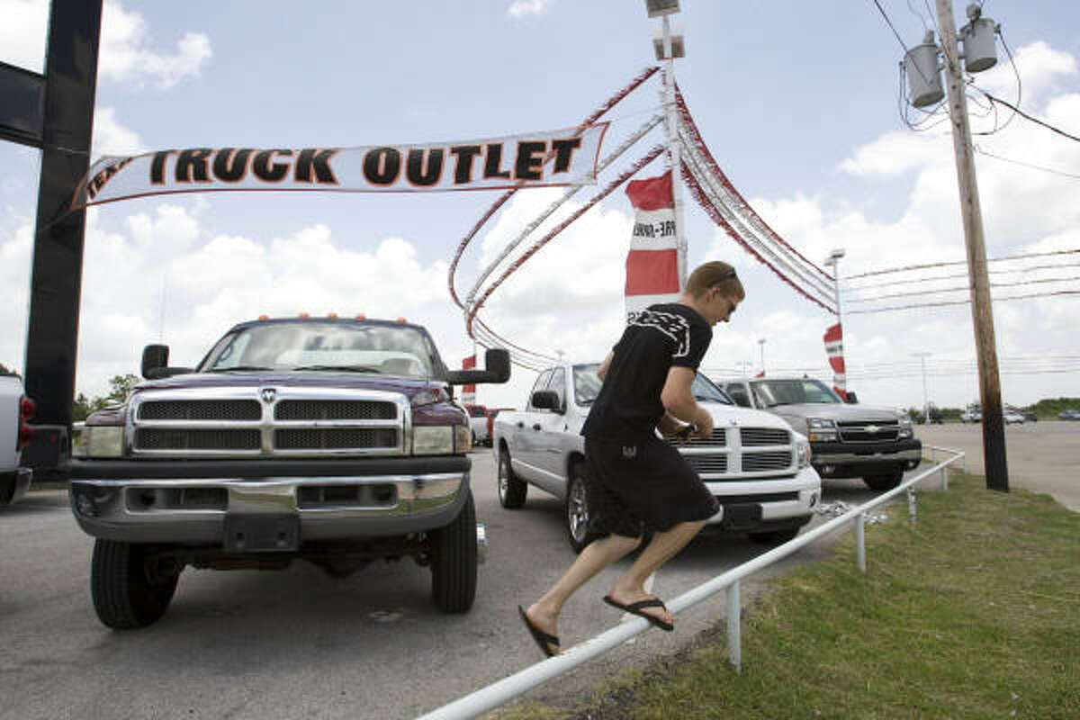 Mike Gallagher looks at a used truck on the Rogers Dodge lot in Alvin during the final day of business.