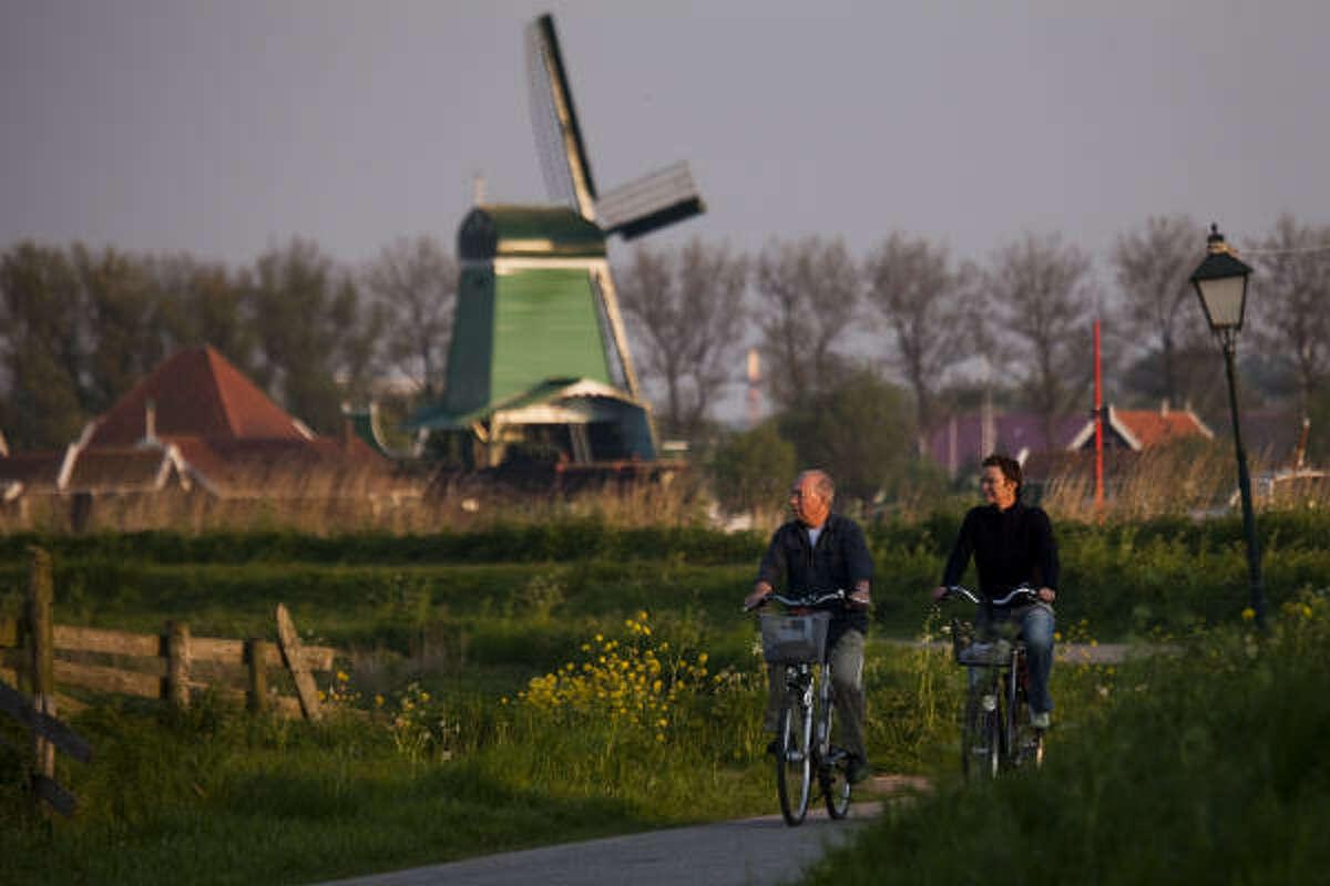 Cyclists ride a path through still-working windmills at Zaanse Schans.