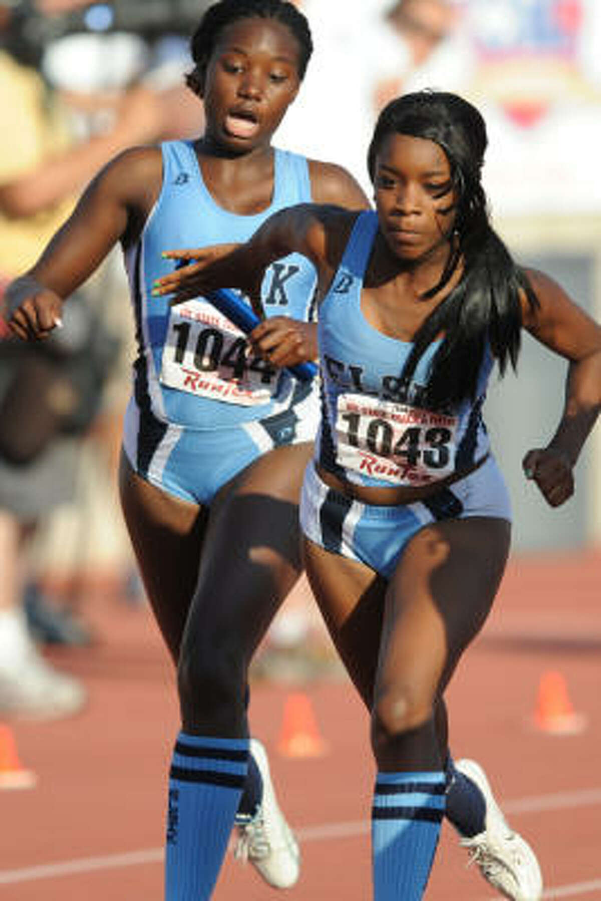 Alief Elsik's April Washington hands off to Alicia Perkins in the 800-meter relay.