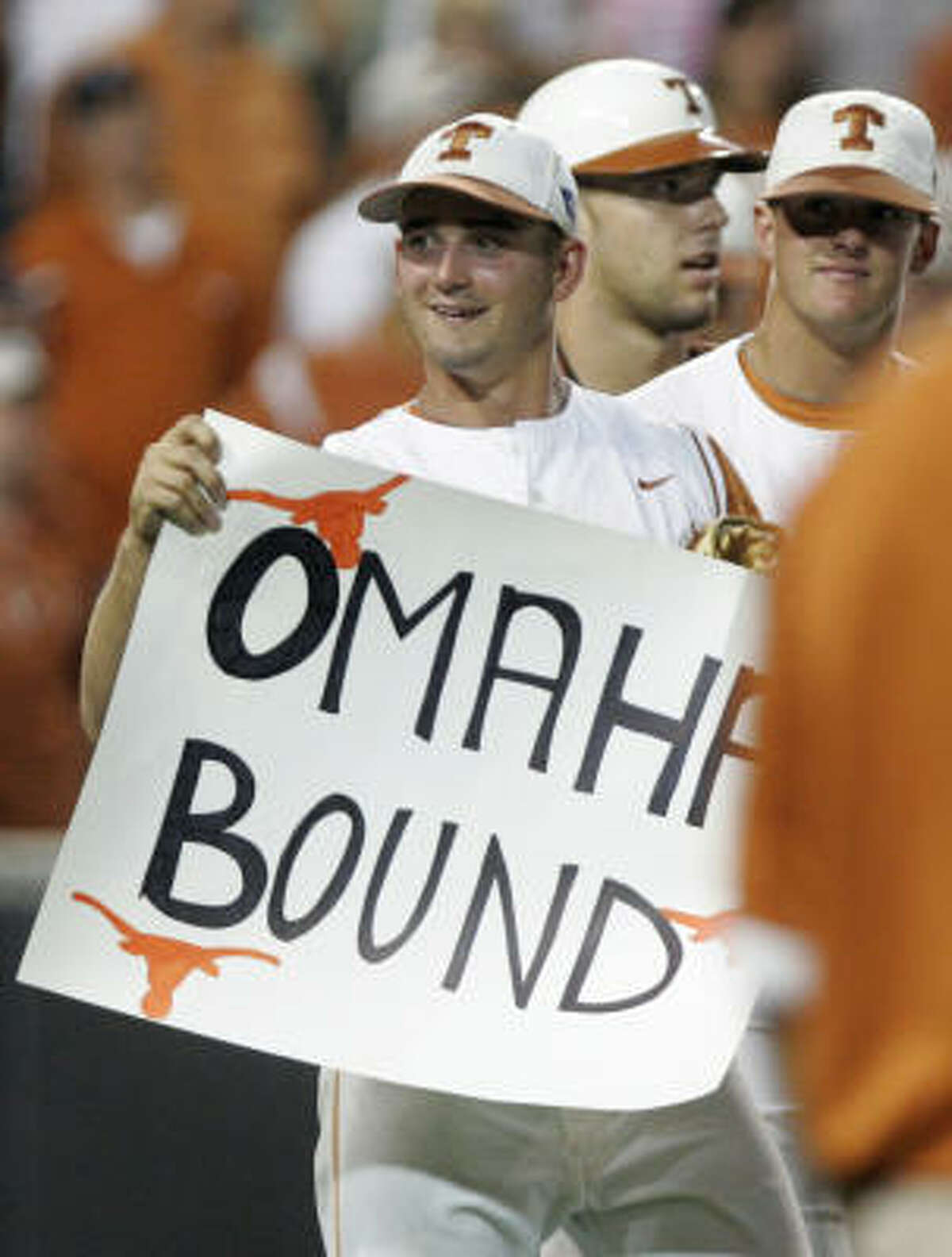Texas second baseman Travis Tucker holds a poster in celebration of Texas' 5-2 win.