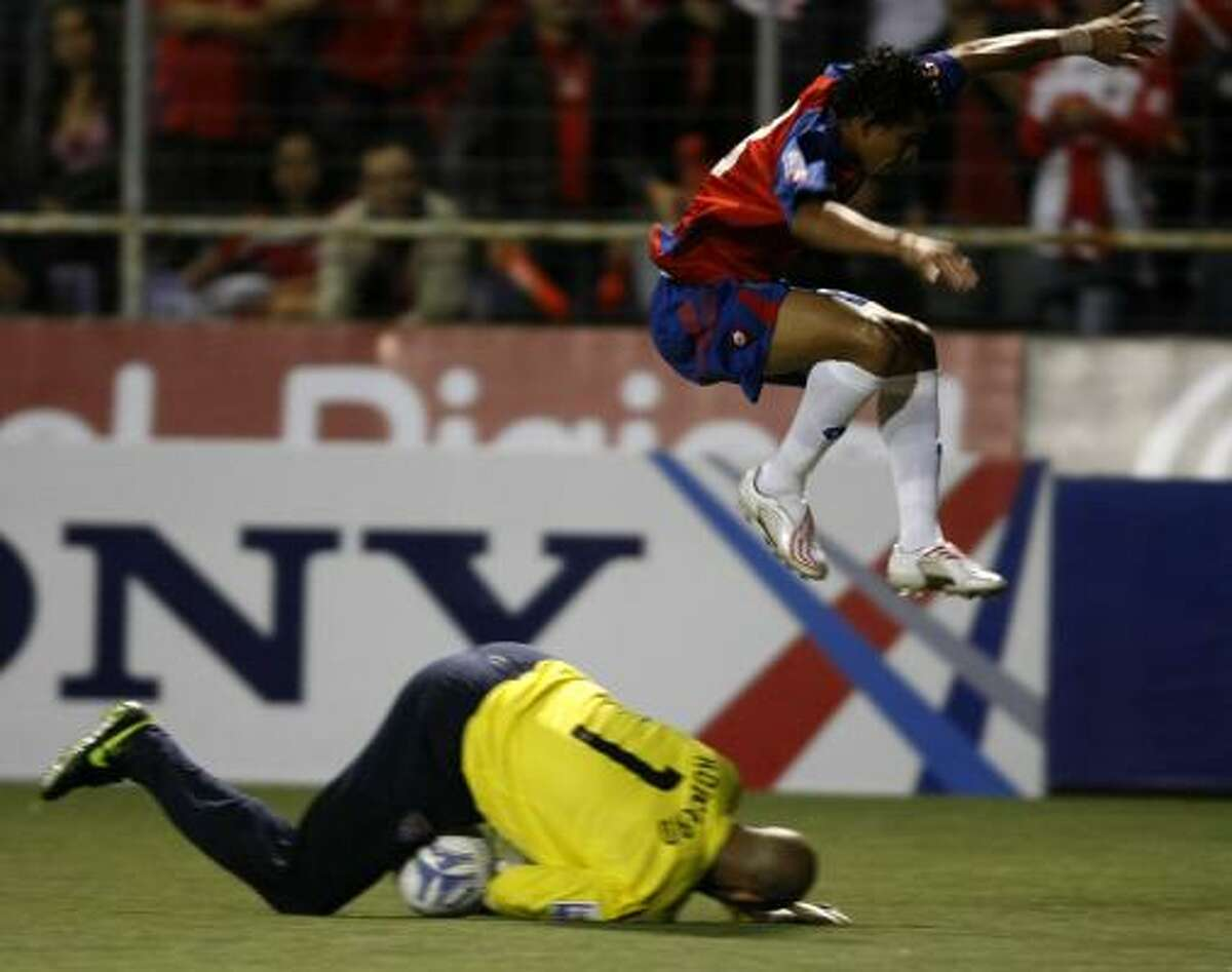 Angel Sirias of Costa Rica jumps over U.S. keeper Tim Howard.
