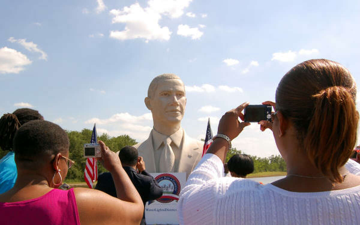 A weekend stop at Pearland's Waterlights District by a bust of President Obama drew crowds and attracted notice from motorists on Texas 288. Alice Weary, left, and her niece Kimberly Weary photograph the 20-foot bust, which was sculpted by David Adickes.