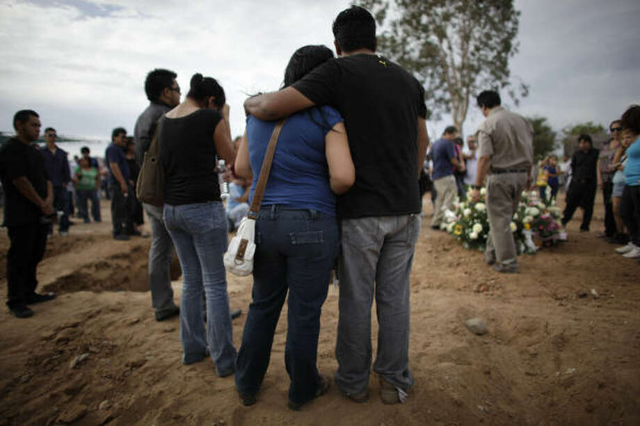 Relatives of Camila Fuentes Cervera watch her service. President Felipe Calderon has wished surviving children a speedy recovery and promised families full government support and a thorough investigation into the fire's cause. Photo: Alexandre Meneghini, AP