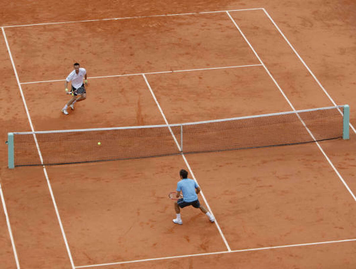 Switzerland's Roger Federer, bottom, and Sweden's Robin Soderling play during their men's singles final match at the French Open at the Roland Garros Stadium in Paris on Sunday.