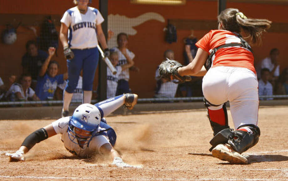Needville third baseman Jenny Stack slides safely into home past Celina catcher Jasmine SanMiguel. Photo: Erich Schlegel, For The Chronicle