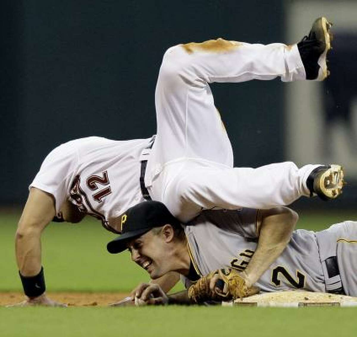 Houston's Ivan Rodriguez (12) is out at second as he falls over Pirates shortstop Jack Wilson (2) after Wilson dove to second base for the force out.