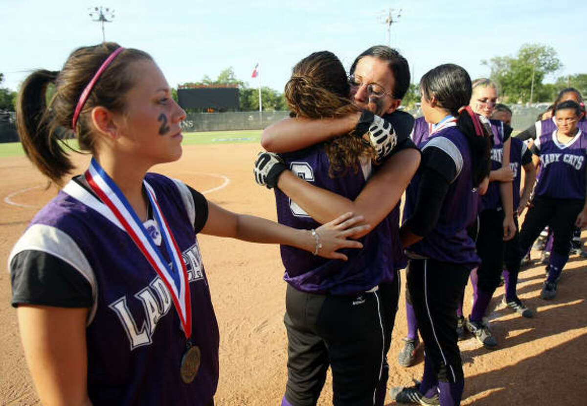 Angleton Wildcats console each other after losing the 4A softball championship to New Braunfels Canyon 4-2.
