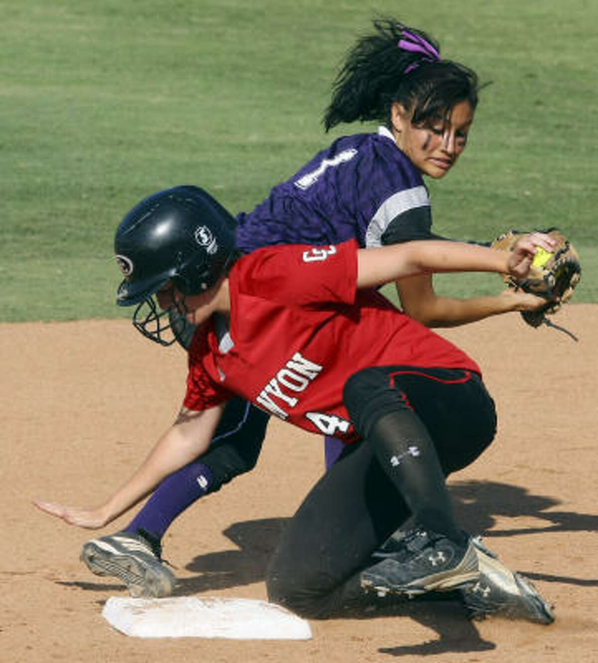 New Braunfels Canyon's Kailee Vrana is safe at second base as Angleton's Gabby Banda applies the tag late.