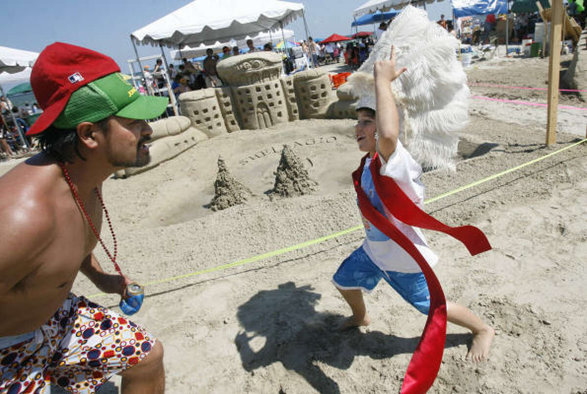 Adam Nguyen and Max Holdman scream to get attention from crowd and judges during the 23rd annual AIA Sandcastle Competition at Galveston's East Beach.