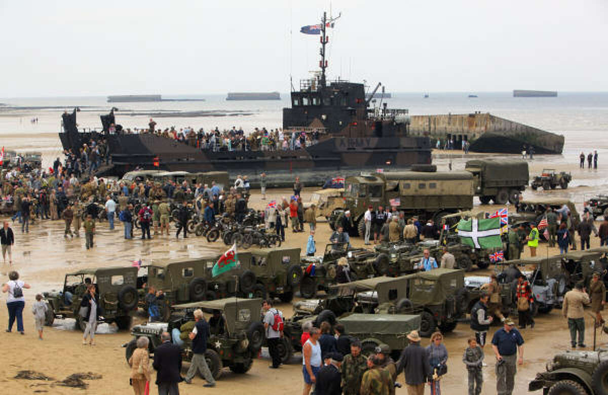 World War Two military enthusiats gather on the beach at Arrowmanches, France. Also during ceremonies, a 12-plane flyover of French, British and American jets boomed above.