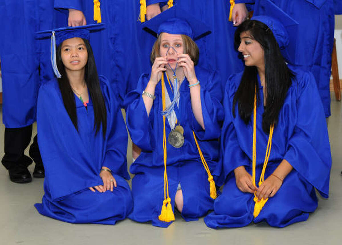 The ceremony at San Jac's south campus was quick, leaving plenty of opportunties to clown around. Dana Lizik drapes her tassel over her nose for a picture with Thao Pham, left, and Herah Hashmi.