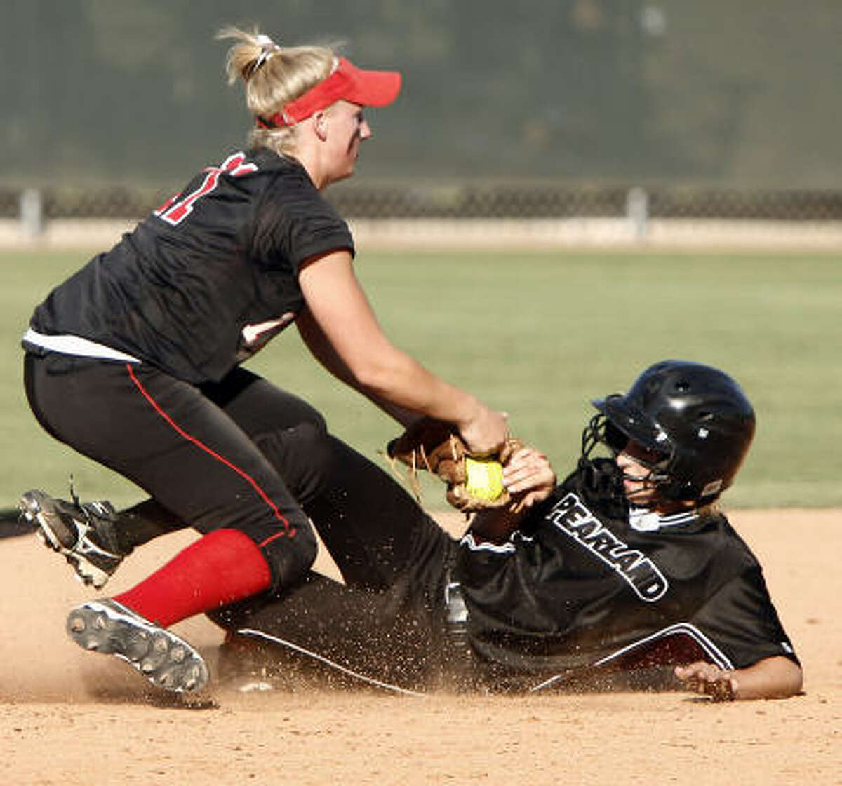 Vista Ridge shortstop Taylor Thom blocks the path of Pearland's Courtney Sams, who was tagged out while attempting to steal second base.