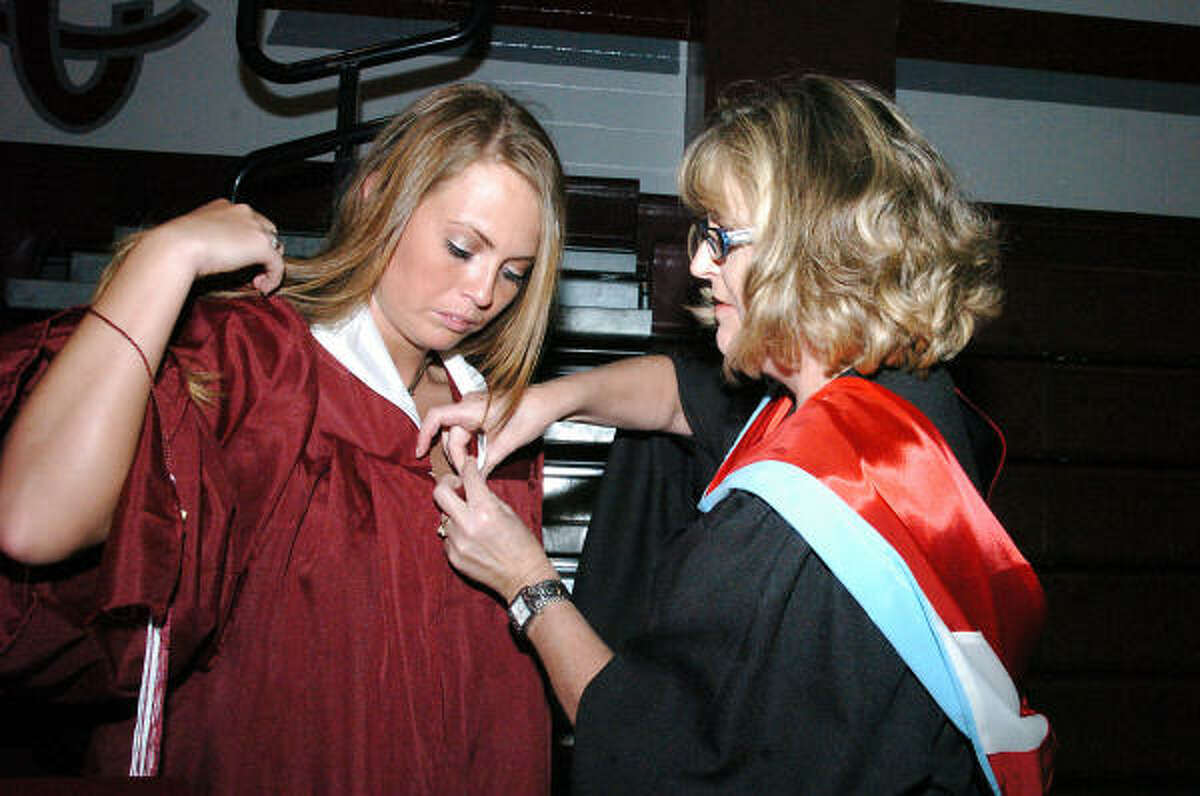 Counselor Laura Stepp helps graduate Natasha Stafford get ready.