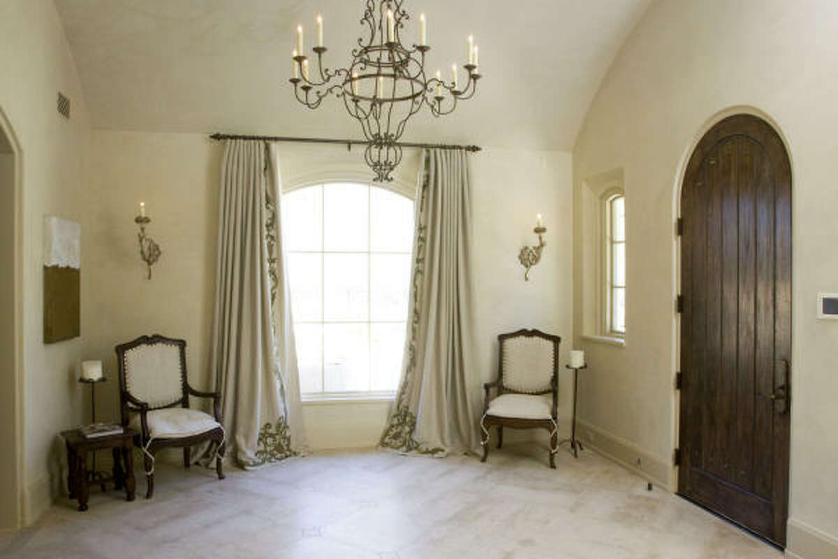 "The Tuscan-style front door opens into a sparse but beautiful foyer with ""Spanish Scroll"" drapes by Florio and 19th-century French armchairs from Area."