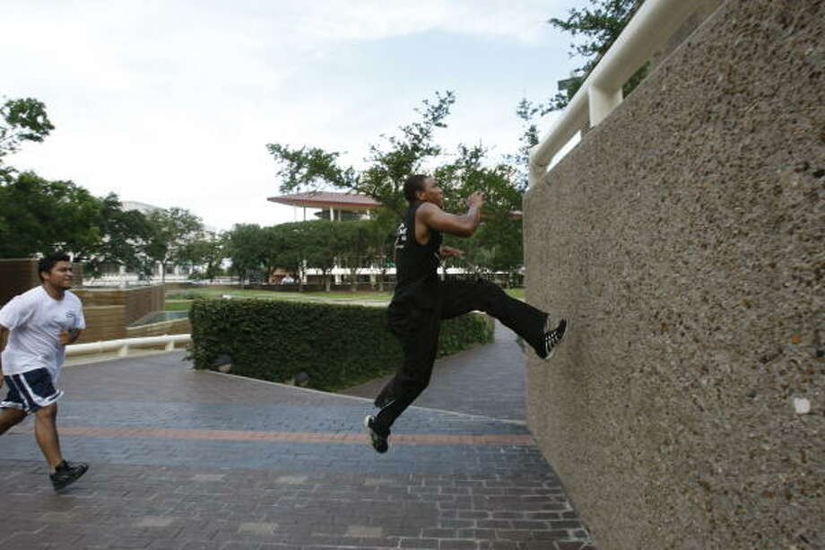Desmund Mitchell, 22, right, the leader of Houston parkour, demonstrates wall climb as Wilbert Chinchilla, 21, pretends to be an attacker chasing Mitchell, as he performs parkour movements at Tranquility Park. Photo: Julio Cortez, Chronicle