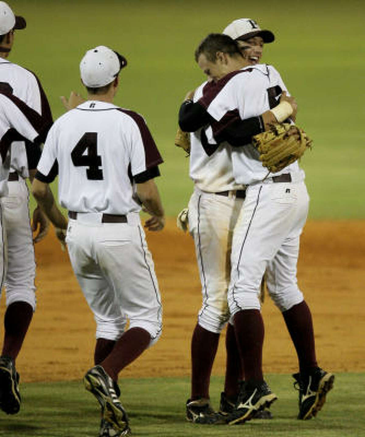 Pearland pitcher Matt Rhodes, right, hugs Kevin Miller while Kyle Cross (4) and the rest of team join the victory celebration.
