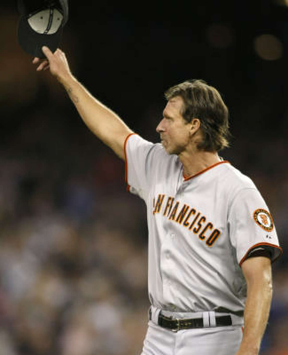 San Francisco Giants pitcher Randy Johnson tips his hat to the crowd as he leaves the baseball game with a 1-1 tie against the Seattle Mariners during the sixth inning at Safeco Field in Seattle, where he played from 1989-98.