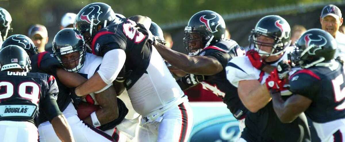 Houston Texans running back Derrick Ward, left in white, is hit by defensive tackle Shaun Cody (95) as he runs the ball during NFL football training camp Saturday, Aug. 6, 2011, in Houston.