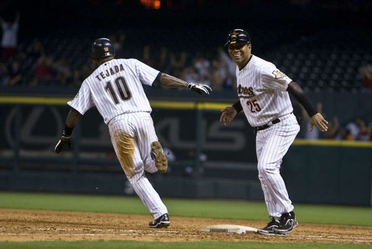 Houston's Miguel Tejada celebrates with first-base coach Jose Cruz as he rounds the bases after his walk-off home run during the 11th inning against the Rockies.