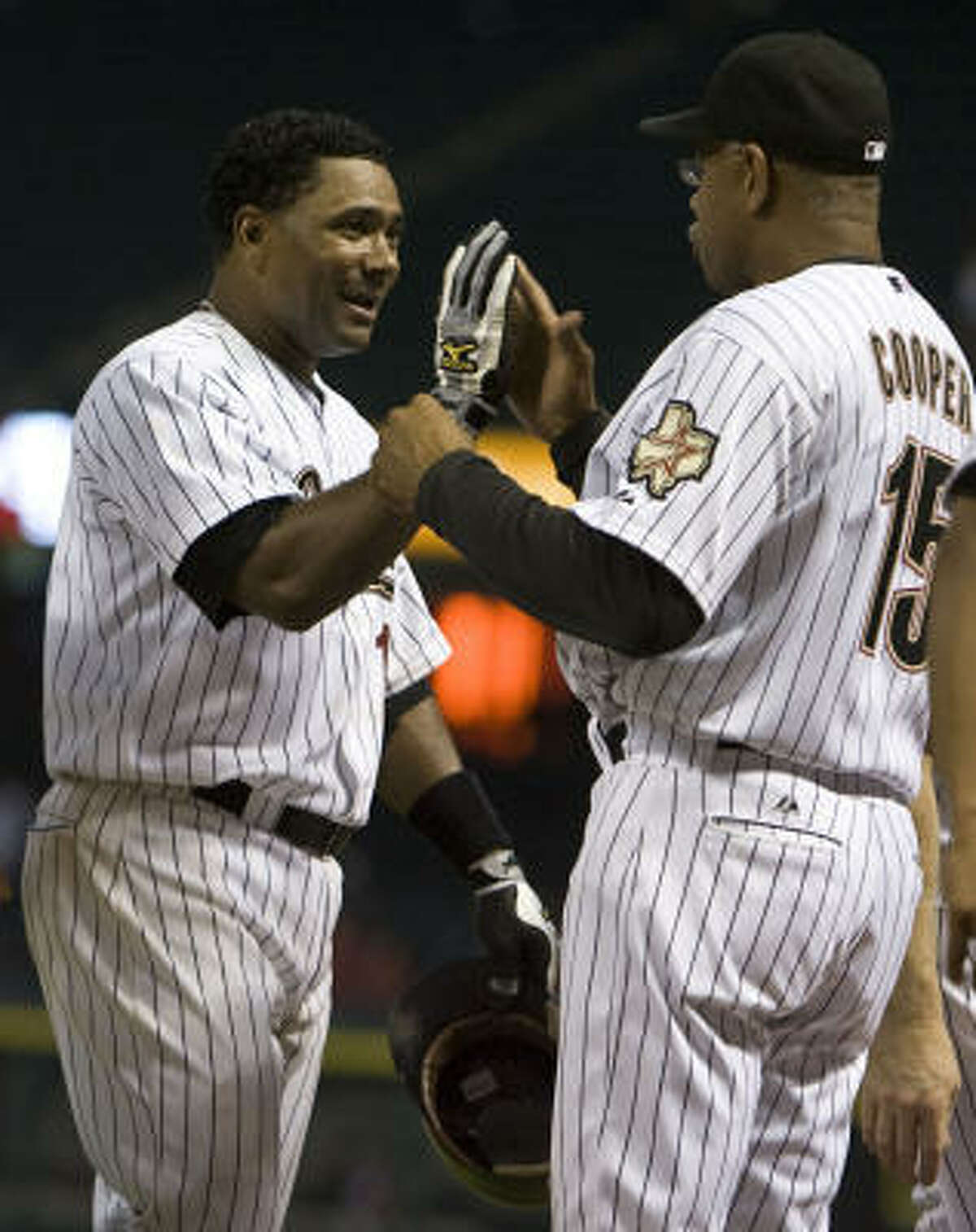 Houston's Miguel Tejada, left, high-fives manager Cecil Cooper after hitting a walk-off home run in the 11th.