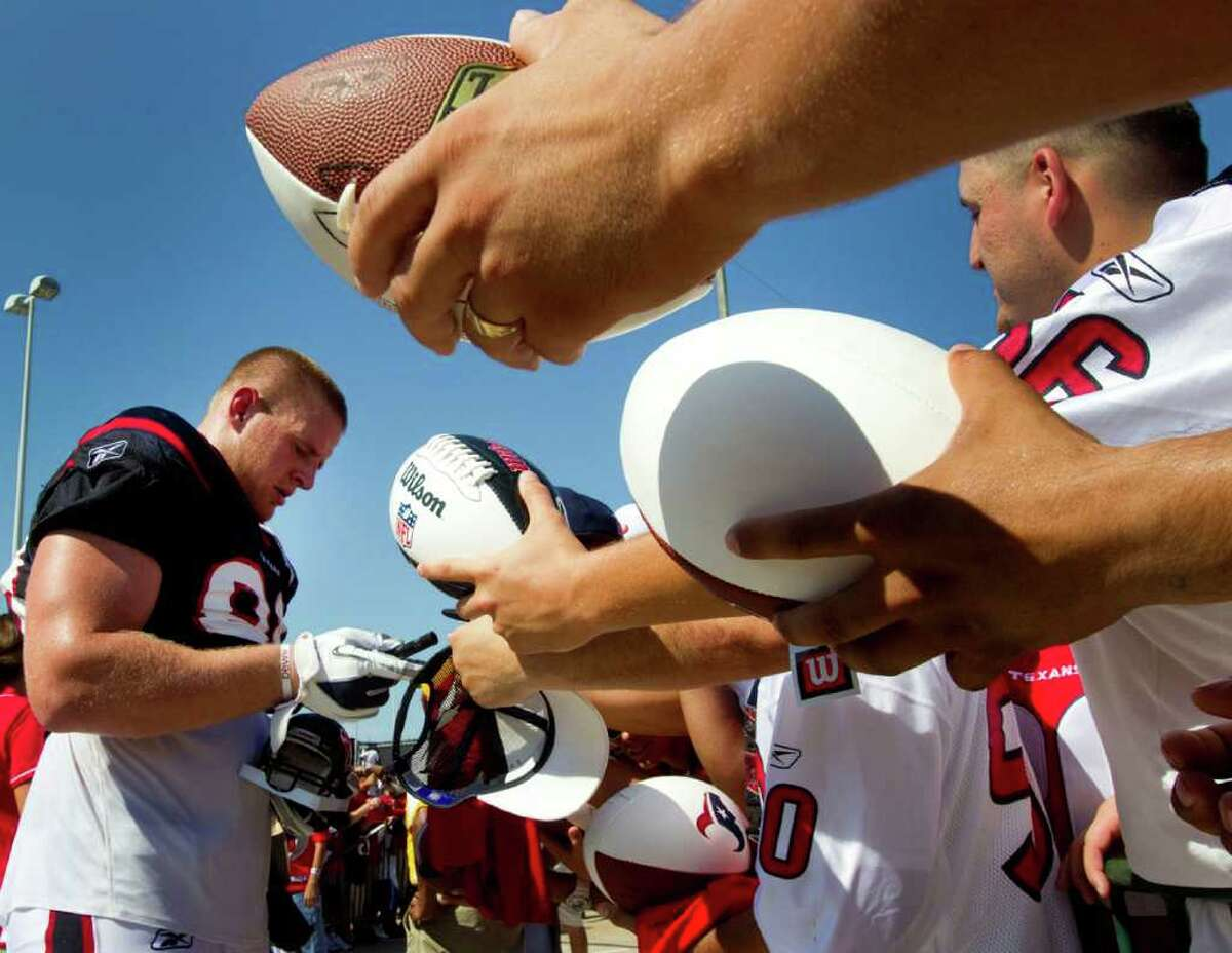 Houston Texans defensive end J.J. Watt (99) signs autographs at the end of practice during an NFL football training camp Saturday, Aug. 6, 2011, in Houston.