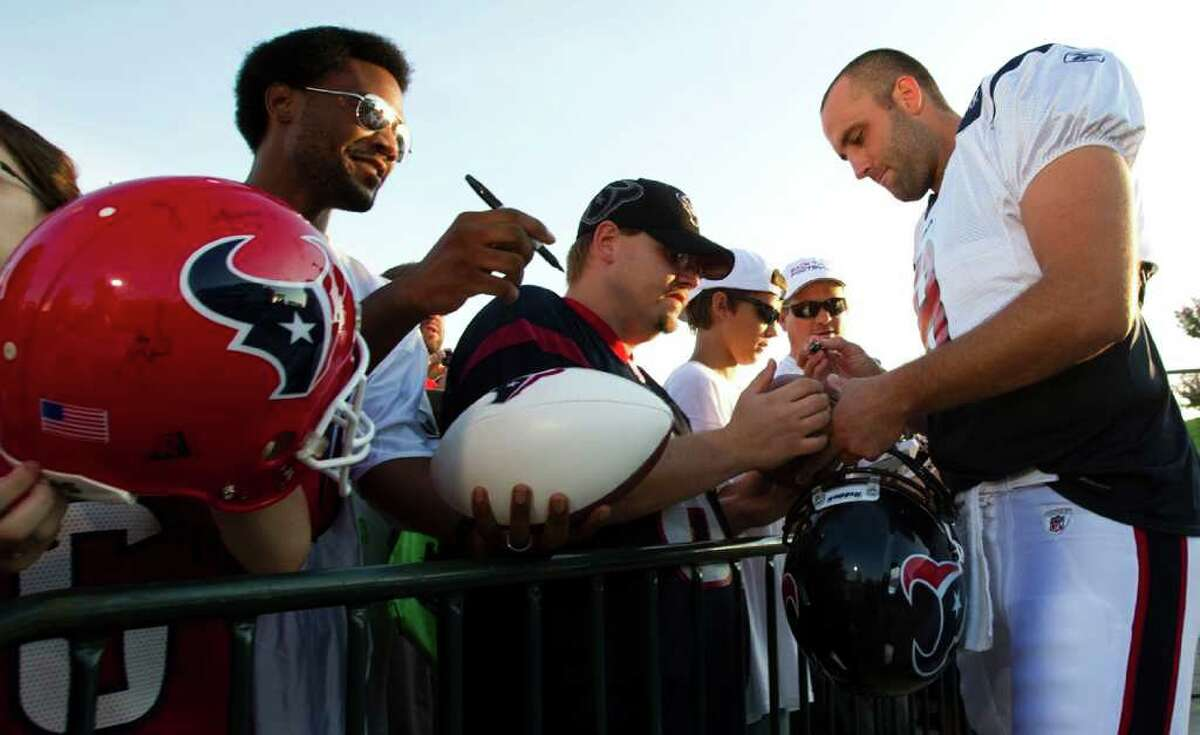 Houston Texans quarterback Matt Schaub, right, signs autographs for fans as he arrives for an NFL football training camp Saturday, Aug. 6, 2011, in Houston.