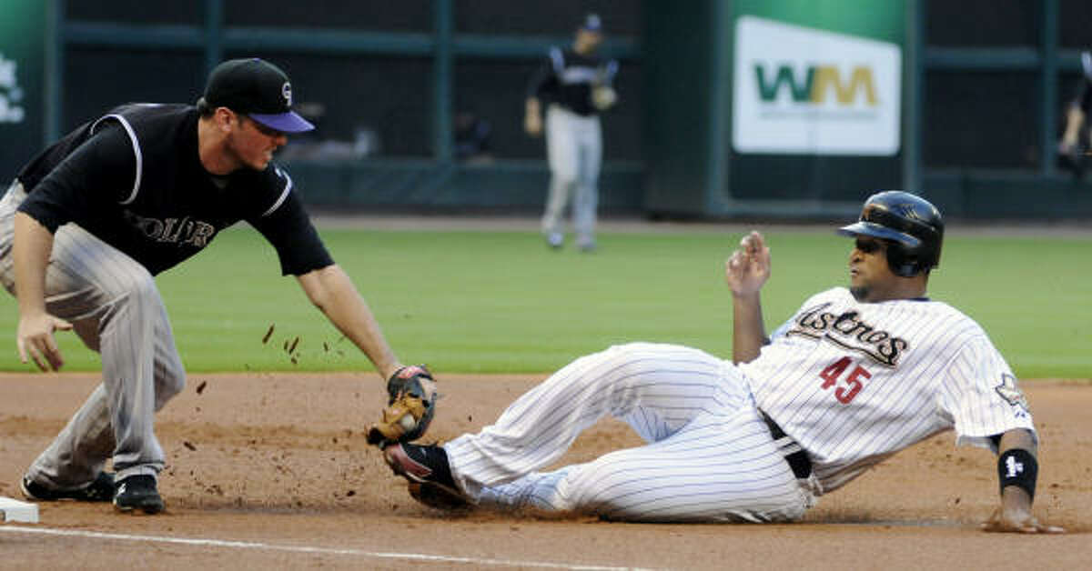 Colorado Rockies third baseman Garrett Atkins tags out Astros left fielder Carlos Lee as he slides into third base to end the first inning.