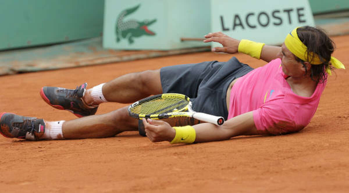 Rafael Nadal tries to get up after taking a tumble while playing against Sweden's Robin Soderling during their fourth round match of the French Open.