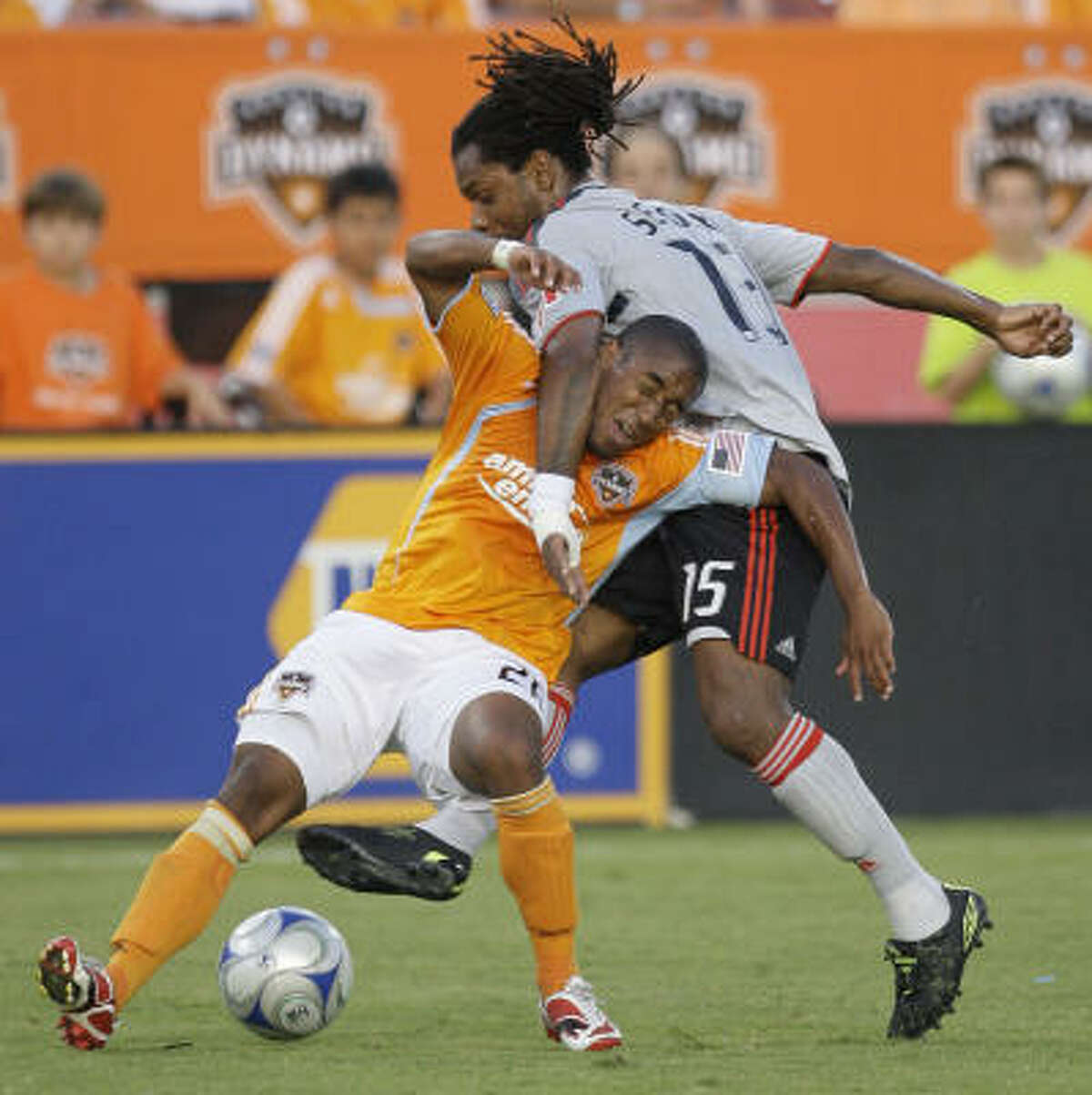 Houston's Corey Ashe, left, and Toronto's Adrian Serioux tangle up for the ball during the first half of the Dynamo's 3-0 win Saturday in Houston.