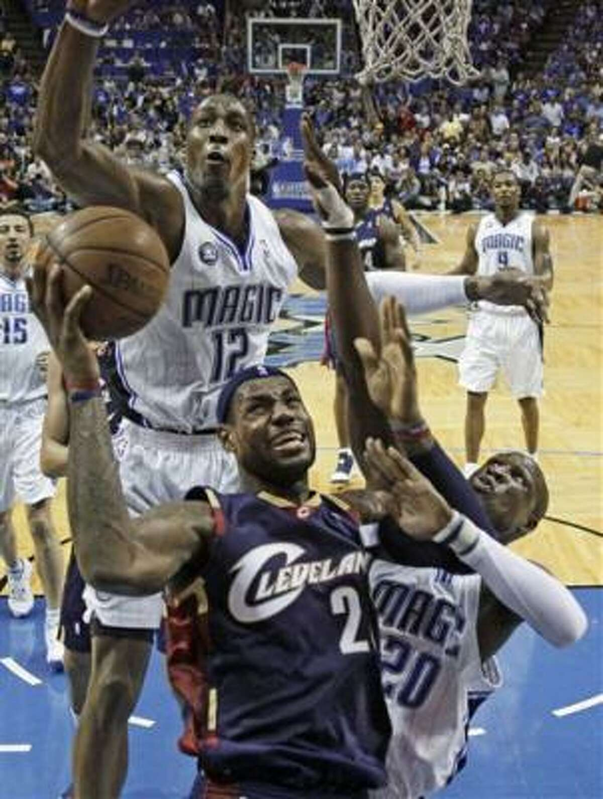 Game 6: Magic 103, Cavaliers 90 Cleveland Cavaliers' LeBron James (23) shoots between Orlando Magic's Hedo Turkoglu, from Turkey,left, and Rashard Lewis (9) in the first quarter.