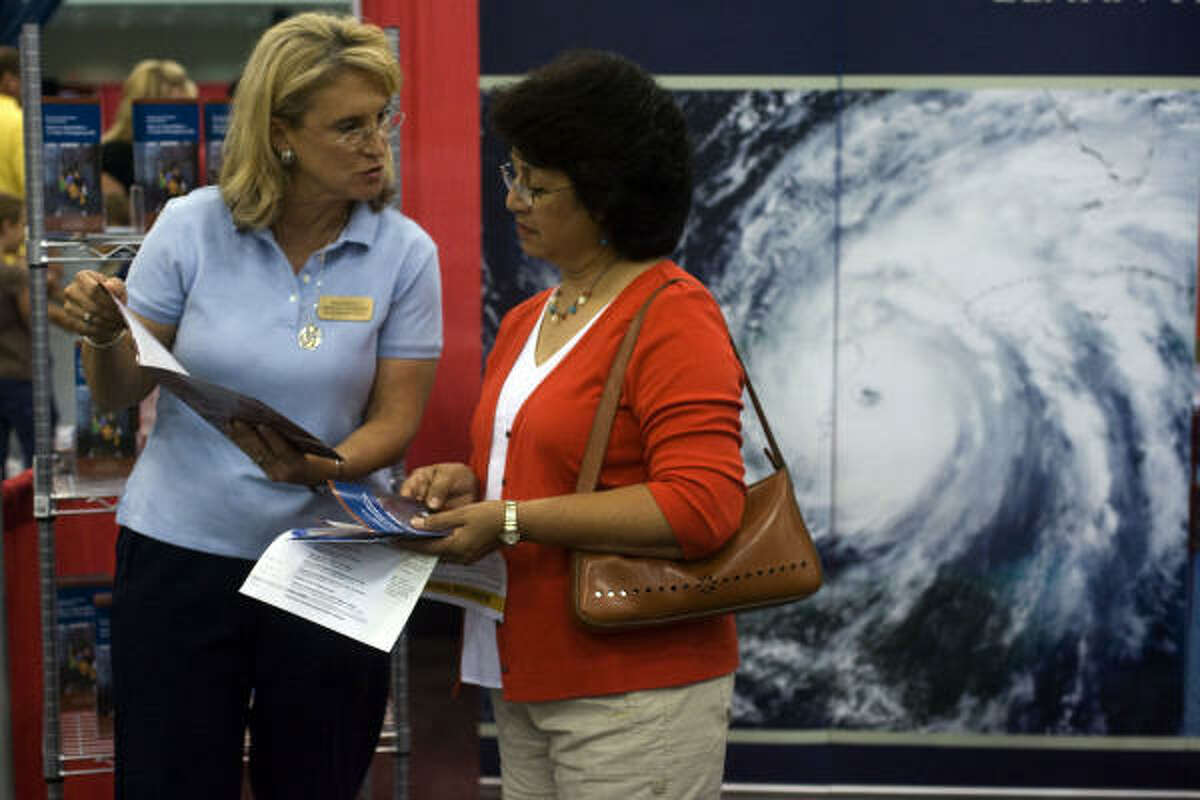 Gloria Parker of Friendswood is given a 72-hour emergency preparedness brochure from Lesley Hagen, with The Church of Jesus Christ of Latter-Day Saints at the 2009 Hurricane Workshop held at the George R. Brown Convention Center.