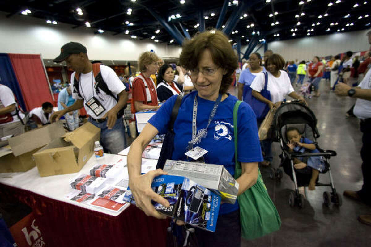 Sarah Keller-Gelbart tries to hold onto all the goods she was given at the American Red Cross booth as the organization handed out batteries, weather radio's and other goods as well as information during the 2009 Hurricane Workshop.