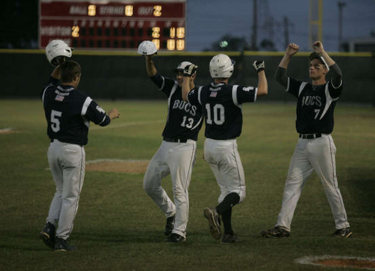 Brazoswood's John Ermis (5) and Will Bedell (10) are congratulated by teammates Jim Basque (13) and Tyler Green (7) after scoring in the bottom of the first inning against Bellaire.