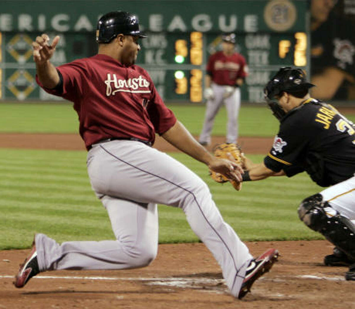 Houston's Carlos Lee scores as Pirates catcher Jason Jaramillo waits for the throw on a base hit by Ivan Rodriguez in the seventh inning.