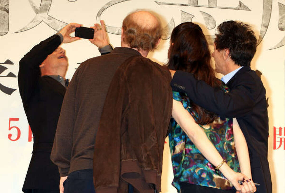 Tom Hanks takes pictures of director Ron Howard, actress Ayelet Zurer and producer Brian Grazer during the Angels & Demons press conference May 7 in Tokyo.