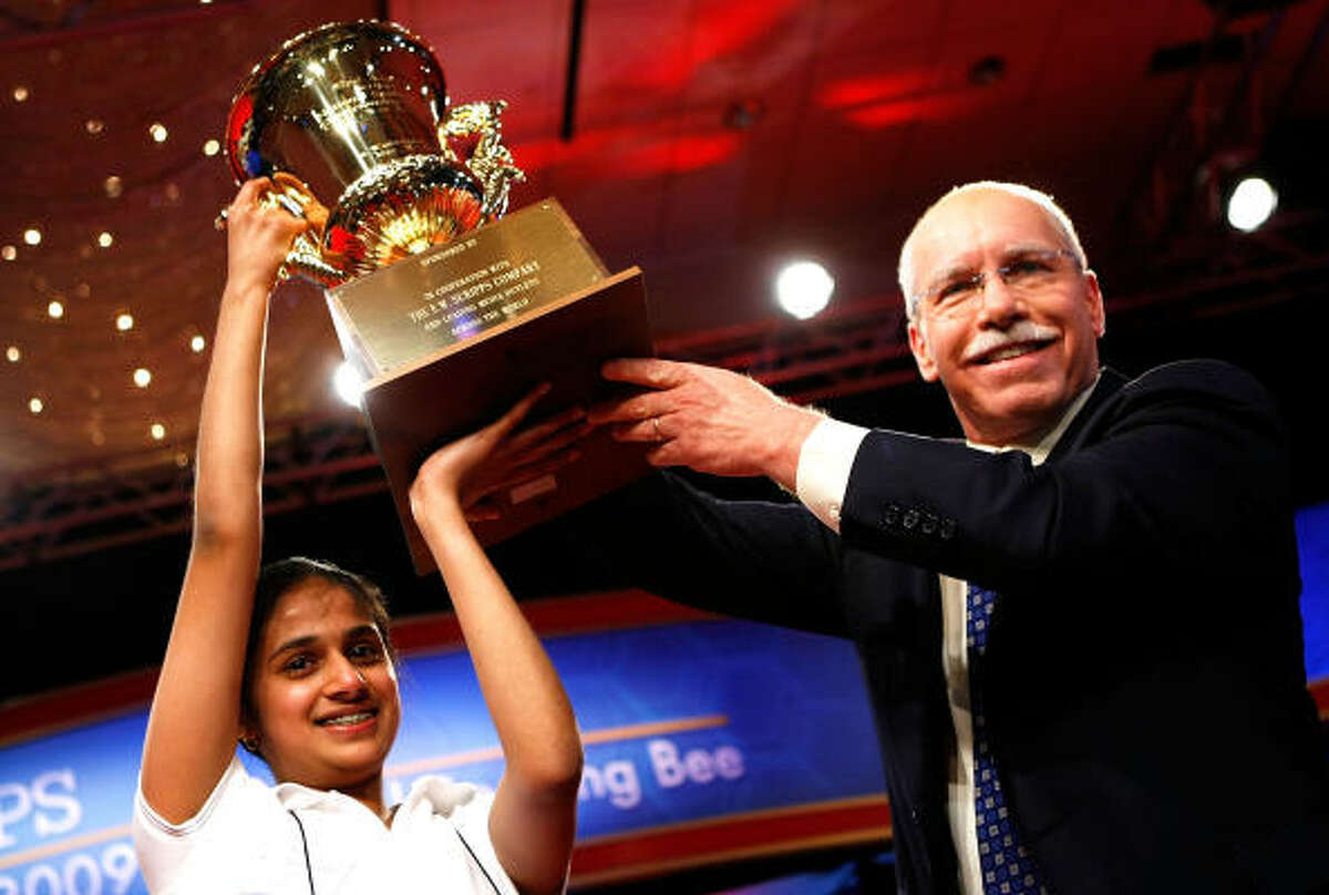 Speller Kavya Shivashankar of Olathe, Kansas, receives the trophy from President and CEO of The E.W. Scripps Company Richard Boehne after she won the 2009 Scripps National Spelling Bee competition.