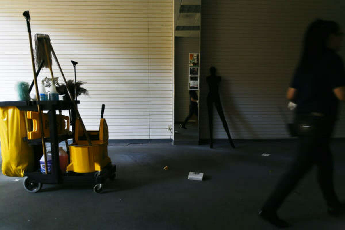A cleaning crew works to clean out the left over goods from a framing store that recently closed.