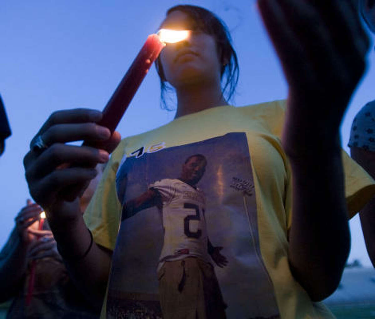 Whitney Hatch holds a candle while wearing a t-shirt with a photo of Jordan Wilson.