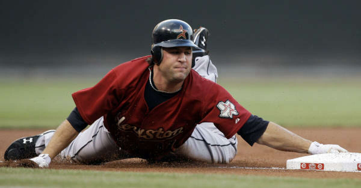 Houston's Lance Berkman slides into third with a triple in the first inning.