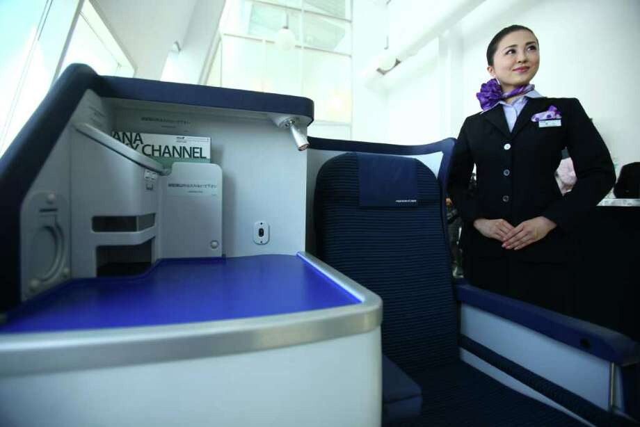 Flight attendant Kyoko Kouokawa shows a mock-up of an international business class seat during the reveal of the first Boeing 787 destined for use by launch customer All Nippon Airways. At left is a small work area, part of the staggered seating arrangement. Photo: JOSHUA TRUJILLO / SEATTLEPI.COM