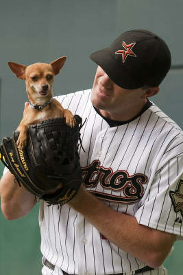 Doug Brocail, who helped coordinate the calendar shoot with is his wife, Lisa, and the Houston Humane Society shows off PeeWee, who is looking for a home. Photo: Smiley N. Pool, Chronicle