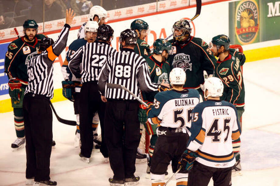 Referees break up an altercation between the Manitoba Moose and Houston Aeros at the MTS Centre. Photo: Boris Minkevich, Winnipeg Free Press