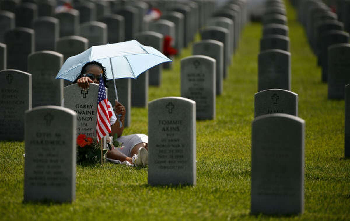 Angeline Bandy sits near at husband's gravestone at the Houston National Cemetery on Monday.