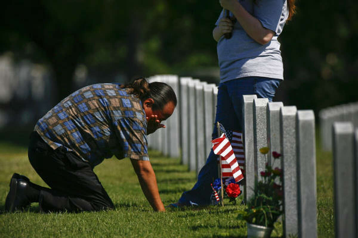 Juan Quesada visits his father's gravestone at Houston National Cemetery.